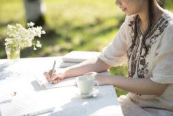 自然の中で手紙を書く女性